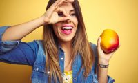 Young beautiful woman eating fresh healthy mango over yellow background with happy face smiling doing ok sign with hand on eye looking through fingers