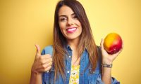 Young beautiful woman eating fresh healthy mango over yellow background happy with big smile doing ok sign, thumb up with fingers, excellent sign